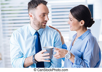 Surprised man smiling while suddenly getting a cup of tea from colleague