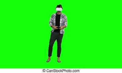 Surprised man uses virtual reality goggles play with joystick. Green screen