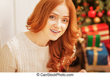 Surprised mature woman looking into camera on christmas morning