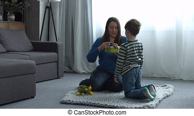 Surprised mother receiving present from her child