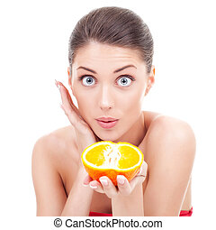 amazed woman holding an orange