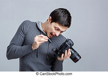 surprised photographer is trying to insert the battery in DSLR d