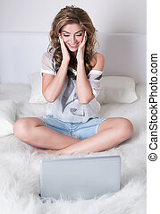 Surprised pretty young girl sitting with silver laptop