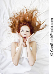 Surprised red-haired girl in bed. Studio shot.