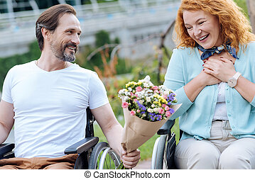 Surprised senior wheelchaired woman getting flowers from her husband