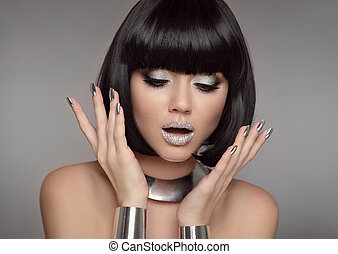 Surprised sexy brunette with open mouth. Glitter eye shadow beauty Makeup, Silver Manicured polish nails. Bob hairstyle. Fashion Style Woman Portrait with black Short Hair isolated on gray background.
