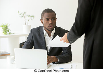 Surprised shocked african businessman getting unexpected notice
