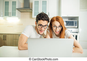 Shocked couple watching something on laptop at home