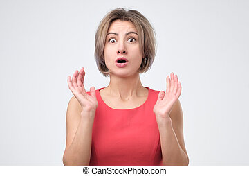 Surprised shocked female wearing red dress, keeping her hand up, opening mouth.
