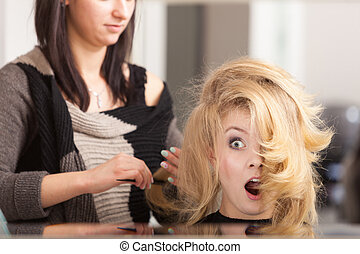 Surprised shocked girl with blond wavy hair by hairdresser. Hairstylist combing female client. Young woman in hairdressing beauty salon. Hairstyle.