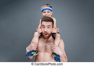 Surprised smiling father holding his little son on shoulders