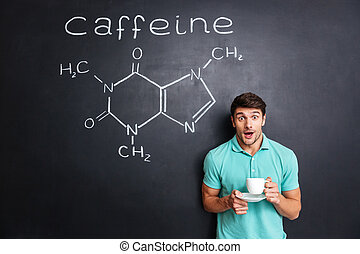 Surprised student drinking coffee over drawn structure of caffeine molecule