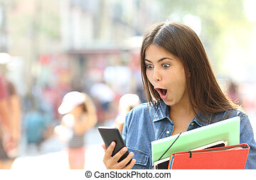 Surprised student girl watching phone content