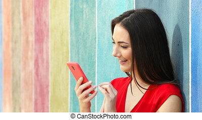 Surprised woman checking phone in a colorful wall -...