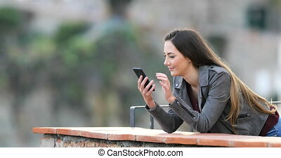 Surprised woman finding phone content in a balcony -...