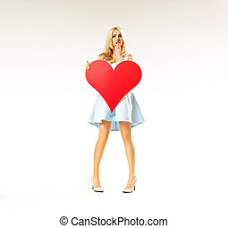Surprised woman holding a big heart