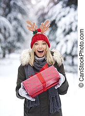 Surprised woman holding Christmas gift