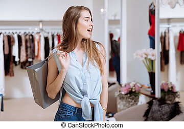 Surprised woman holding shopping bag and standing in clothing store