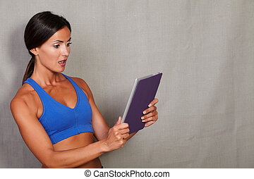 Surprised woman holding tablet with open mouth