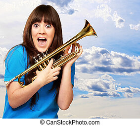 surprised woman holding trumpet, outdoor