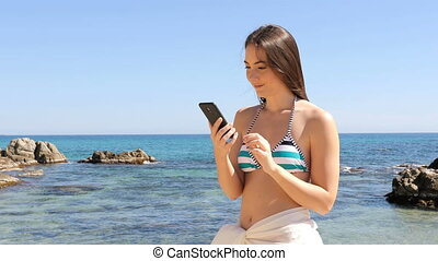 Surprised woman in bikini reading phone content on the beach...