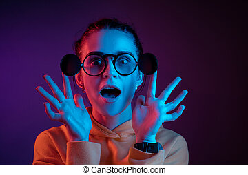 Surprised woman in glasses looking at camera