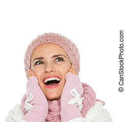Surprised woman in knit winter clothing looking up on copy space