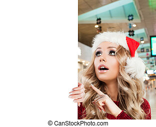 Surprised woman in Santa hat holding white blank paper signboard with copy space on shopping mall background. Christmas and New Year sale and offer concep