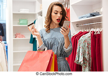 Surprised woman in shop using smartphone