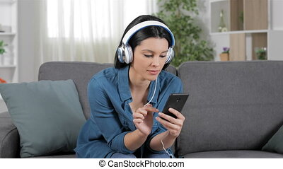Surprised woman listening to music from cell phone sitting...