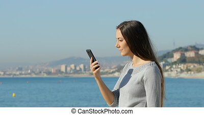 Surprised woman on phone on the beach - Side view portrait...