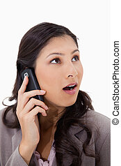 Surprised woman on the phone against a white background