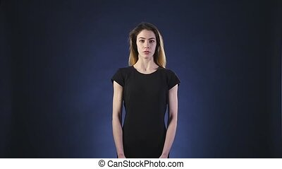 Surprised woman over dark background slow motion