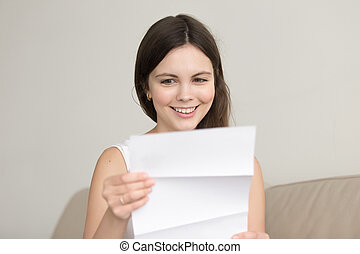 Surprised woman reading letter with unexpected good news, feelin