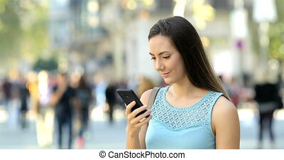 Surprised woman reading phone content in the street -...