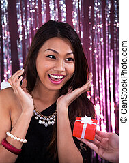 Surprised Woman Receiving Gift In Restaurant