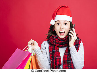 surprised Woman shopping for christmas gifts and talking the phone