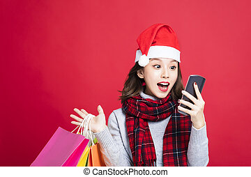 surprised Woman shopping for christmas gifts and watching smart phone