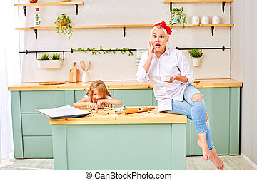 Surprised woman sitting on the table near a cute daughter