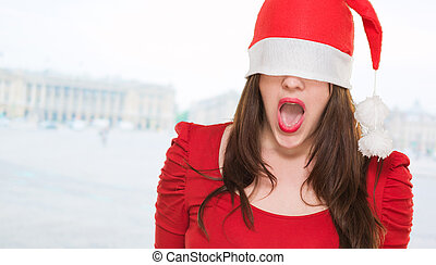 surprised woman with a christmas hat covering her eyes