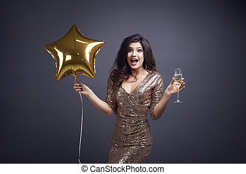 Surprised woman with balloon and champagne flute
