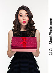 Surprised woman with makeup in retro style holding gift box