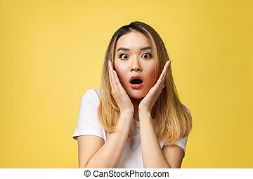 Surprised young asian woman face isolate over yellow background.