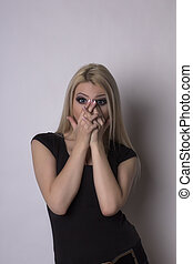 Surprised young blonde woman. Studio shot
