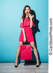 Surprised young brunette woman holding shopping bag. - Image...