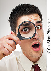 loupe - surprised young business man looking through loupe...