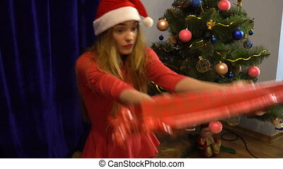 surprised young girl in santa hat with big long christmas gift