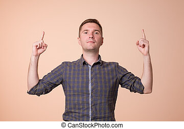 Surprised young man pointing up with two hands. Hey look up concept