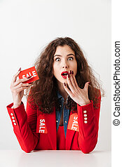 Surprised young shopaholic woman holding sale sign
