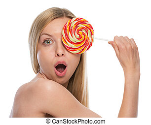 Surprised young woman holding lollipop